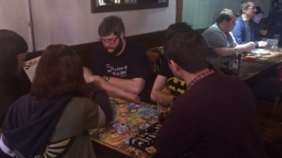 A group of regulars and new attendees join to play a new game together